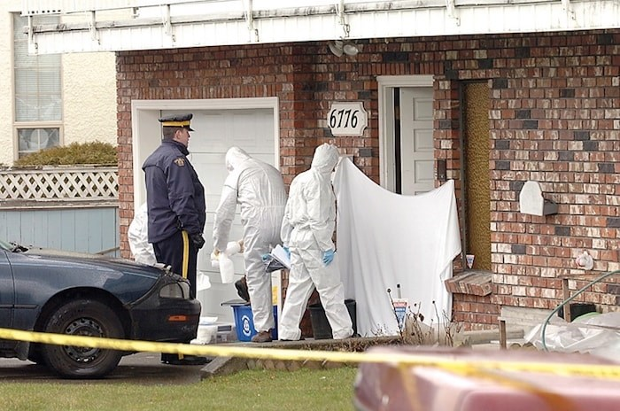 Homicide investigator scour a unit in a Colborne Avenue fourplex in March 2009 after the discovery of Kimberly Halgarth's body inside.  (Burnaby Now file photo)