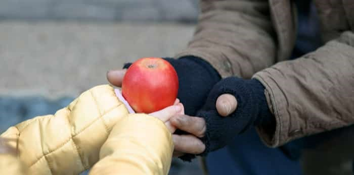 Kind little child gives apple to a homeless person / Shutterstock