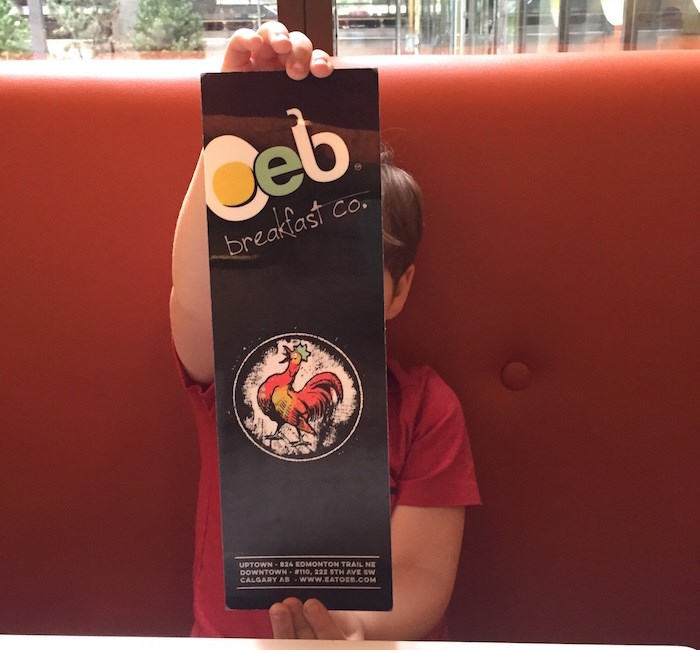 That just might be my kid modelling the OEB menu at their downtown Calgary location. Okay, fine, it is my kid. (Lindsay William-Ross/Vancouver Is Awesome)