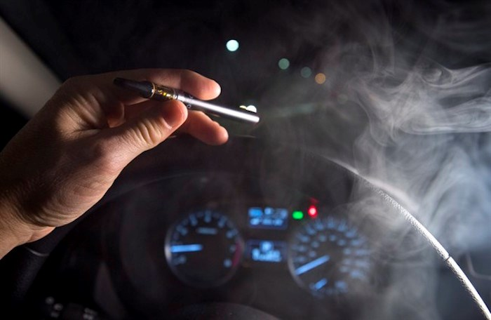 In this photo illustration, smoke from a cannabis oil vaporizer is seen as the driver is behind the wheel of a car in North Vancouver, B.C. Wednesday, Nov. 14, 2018. THE CANADIAN PRESS /Jonathan Hayward