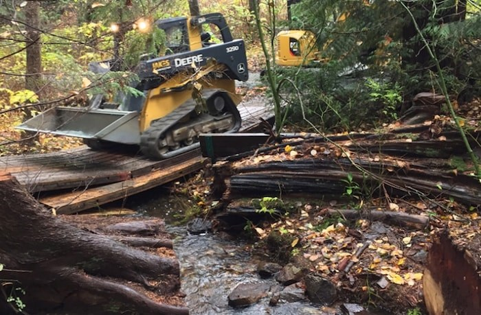 This photo shows Eagle Creek and a cracked bridge with a piece of heavy equipment crossing it.