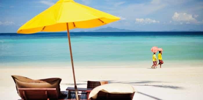 Two women pass by the yellow beach umbrella / Shutterstock