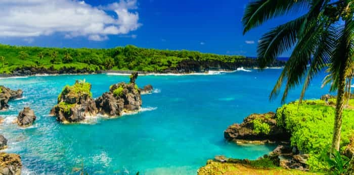 Waves breaking on the rocks on a sunny day on the Road to Hana, Maui / Shutterstock