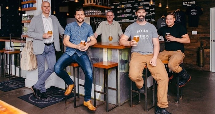 Pictured from left: Sean Hodgins, president of Century Group, Adam Mills, sales and marketing director and co-founder of Four Winds Brewing Company, Greg Mills, co-founder, Brent Mills, brew master and co-founder, and Kylo Hoy, head brewer. File photo.