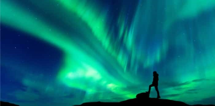 Aurora borealis with silhouette standing man on the mountain / Shutterstock