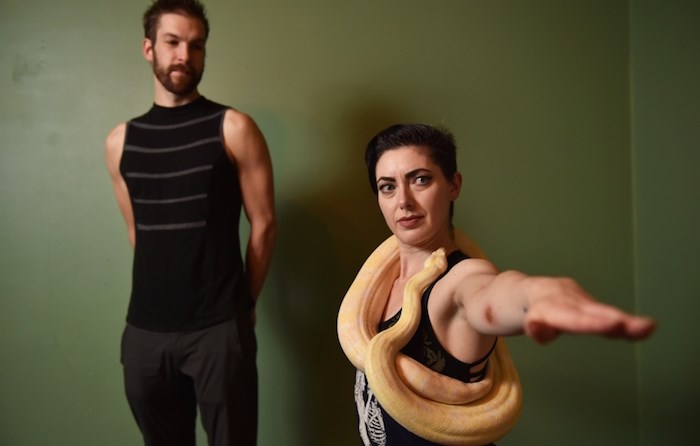 Lukas Knab and Tristan Risk alongside Eros, a nearly six foot long albino boa constrictor. The pair are bringing snake yoga to Vancouver for the first time in January. (Vancouver Courier)