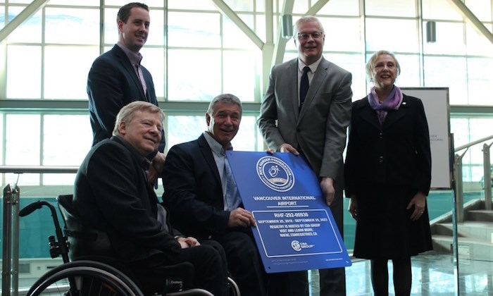 Richmond's Rick Hansen and (centre) presents YVR's Craig Richmond with a plaque recognizing its