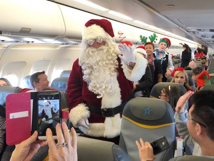 Santa makes his way through the plane on the 14th annual Flight with Santa, a partnership between Air Transat and the Children's Wish Foundation. About 30 wish kids and their families took to the skies Dec. 5 on a mission to find Santa and bring him back to Vancouver. Photo Jessica Kerr