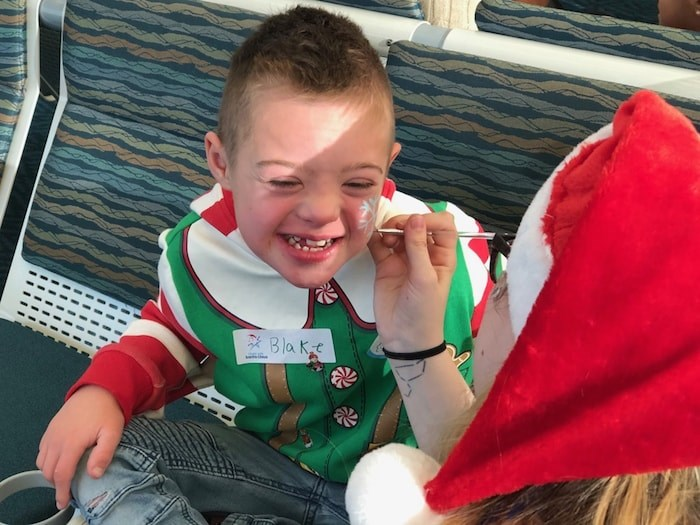 Blake Devisser, 10, gets his face painted as he waits to board the annual Flight with Santa Claus. Photo Jessica Kerr