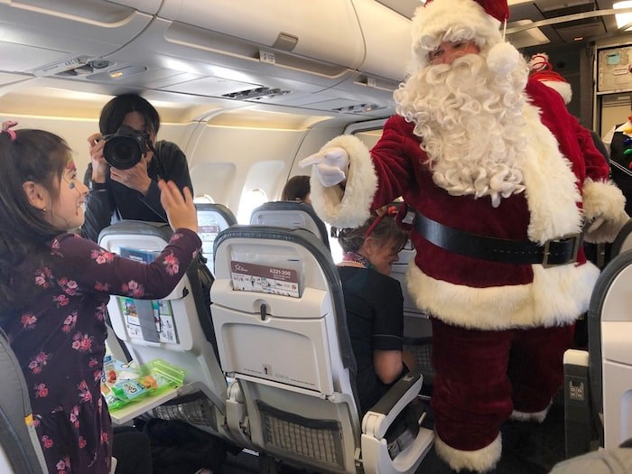 Aria Tejani, 4, shares a moment with Santa Claus as he makes his was through the plane. Photo Jessica Kerr