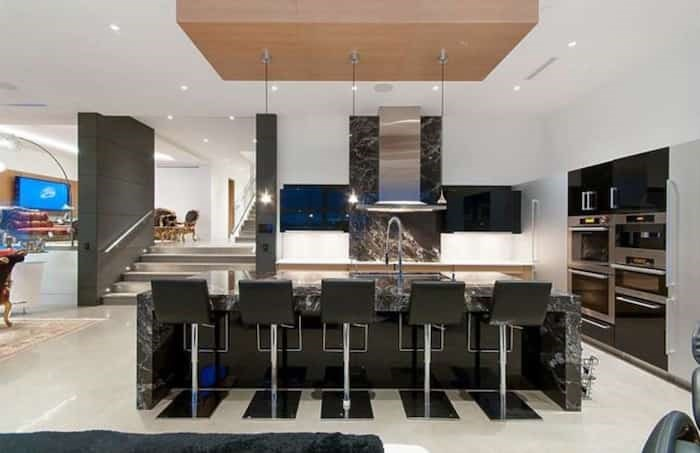 The kitchen in the great room of this split-level home is designed by European kitchen designers Poggenpohl and has black marble countertops and backsplash. Listing agent: Nafiseh Samsam