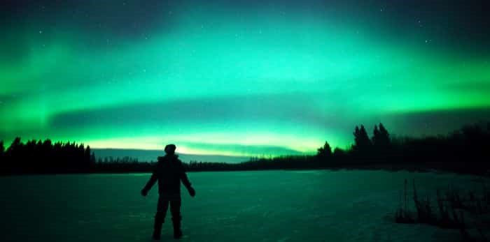 The ghostly colors of the aurora borealis captured above an unidentified person standing on a frozen lake in northern Canada / Shutterstock