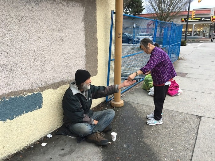 Gia Tran stops and gives some money to a person asking for change. Photo Grant Lawrence