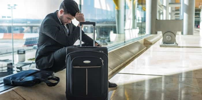 Businessman angry at the airport waiting his delayed flight with luggage / Shutterstock