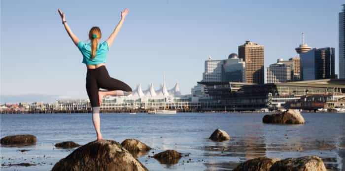Woman practicing yoga in Stanley Park with city skyline in the background / Shutterstock
