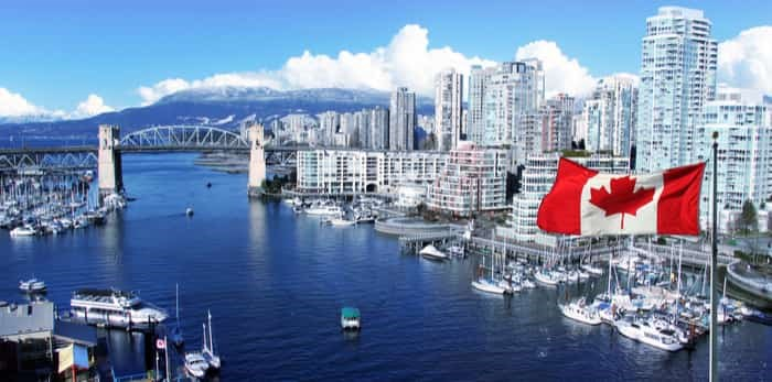 Canadian flag in front of view of False Creek and the Burrard street bridge in Vancouver, Canada. / Shutterstock