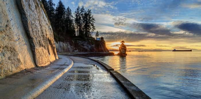 Seawall and rock wall at sunset, with famous Siwash Rock in the sea water, Stanley Park, Vancouver / Shutterstock