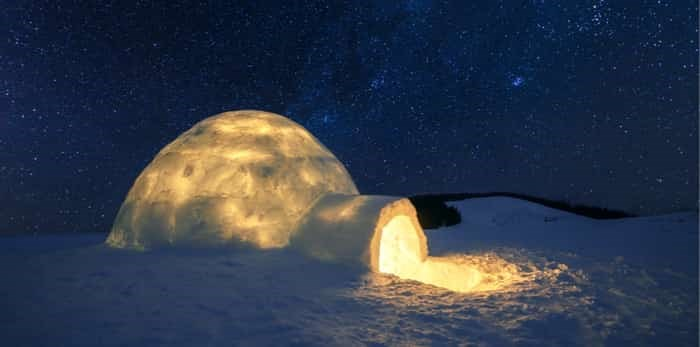 Wintry scene with snowy igloo and milky way in night sky / Shutterstock