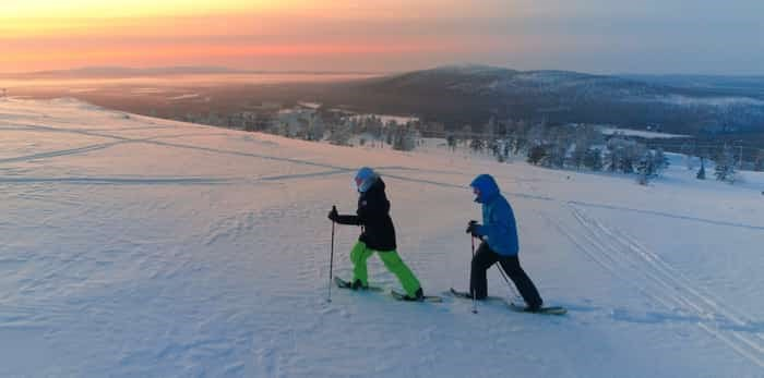 Active couple snowshoeing up a mountain slope / Shutterstock