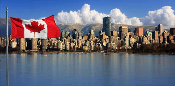 Canadian flag in front of the beautiful city of Vancouver / Shutterstock