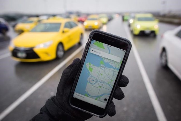 The Uber app is displayed on an iPhone as taxi drivers wait for passengers at Vancouver International Airport, in Richmond, B.C., on Tuesday March 7, 2017. THE CANADIAN PRESS/Darryl Dyck