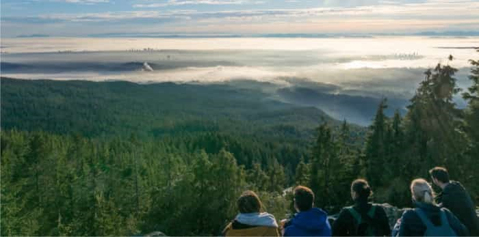 Group of hikers enjoying the panoramic view over the clouds from dog mountain in Vancouver on a sunny afternoon / Shutterstock