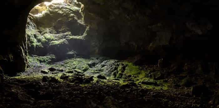 Dark cave with a bright daylight spot of exit / Shutterstock