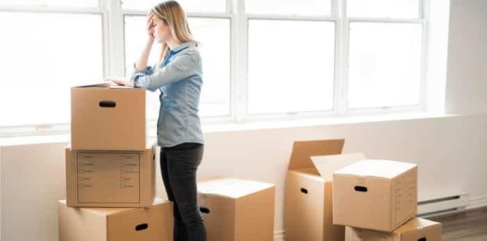 Woman frustrated, surrounded with boxes on a lonely move / Shutterstock