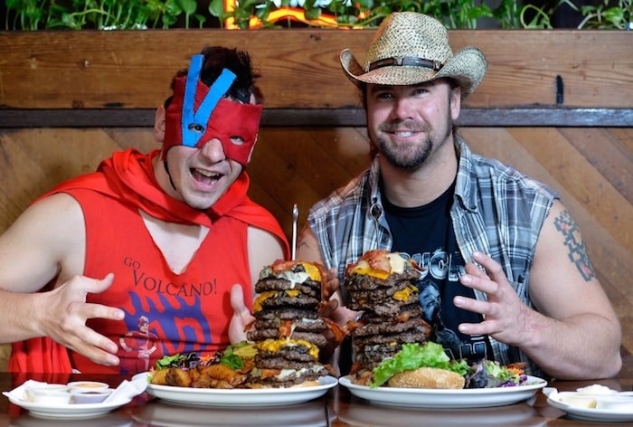 The Volcano, left, and Big Daddy Buck Lighting, who are among the wrestlers competing in the 20-person Royal City Rumble on March 30 in New Westminster, dropped by Burger Heaven on Saturday as part of a challenge to see who could eat a rumble version (10 patties) of Burger Heaven's Ernie's Mile High, eight-patty burger. Photo by Jennifer Gauthier