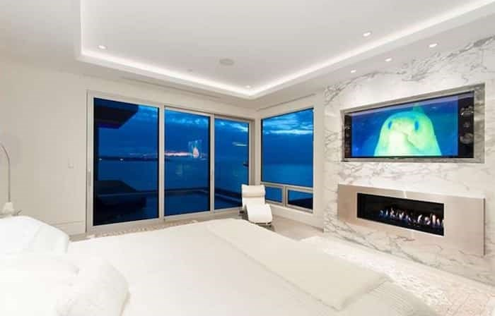 The master bedroom has a contemporary linear fireplace with more marble on the huge surround, plus sliding doors to an upper-level deck. Listing agent: Nafiseh Samsam