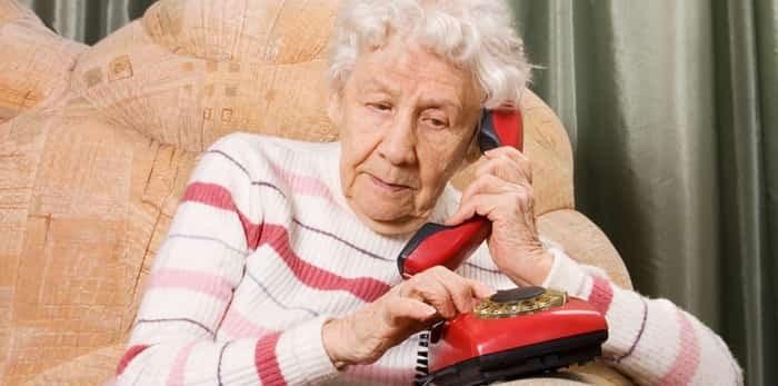 An elderly woman speaks on phone / Shutterstock