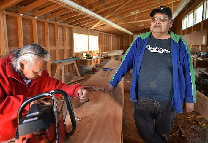 Musqueam Indian band carver William Dan, at right, works on what will become a 20-foot welcome post at the carving pavilion adjacent to Britannia secondary. Photo by Dan Toulgoet