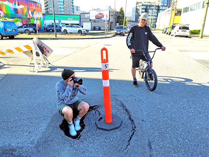 A man and his friend take advantage of the sinkhole on a sunny afternoon. Photo Bob Kronbauer