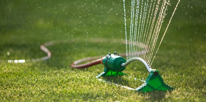 A sprinkler waters a lawn. Metro Vancouver will be on restricted water use from May 1 to Oct. 15. Photo via Shutterstock.