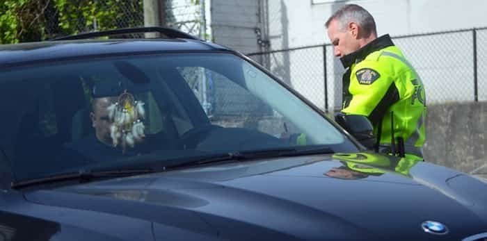 An Integrated Road Safety Unit officer writes a driver a ticket for an infraction in a construction zone in Burnaby Monday. Photo:; Cornelia Naylor