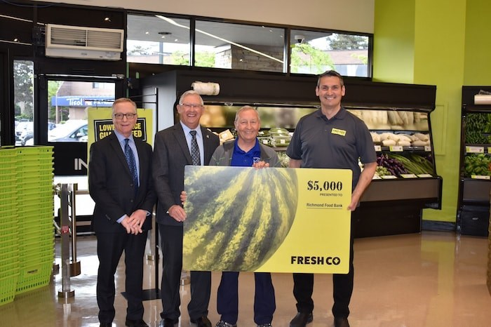 FreshCo general manager Rob Adams (far left) and owner of the Broadmoor location Scott Marshall (right) present Richmond Food Bank with a check for $5000. Photo by Alvin Chow