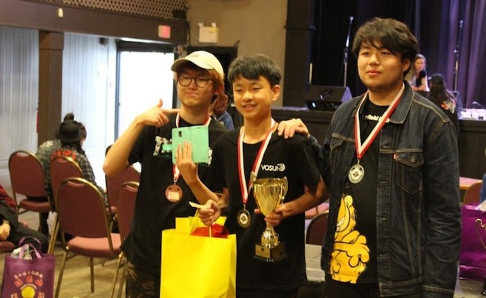 Richmond's Terrance Wang (centre) picks up his national title prizes. Photo submitted.