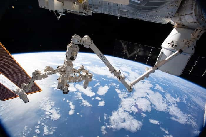 The Canadarm2 robotic arm with its robotic hand, also known as Dextre, attached for fine-tuned robotics work extends across the frame as the International Space Station orbited 256 miles above the Atlantic Ocean. Photo: NASA Johnson /