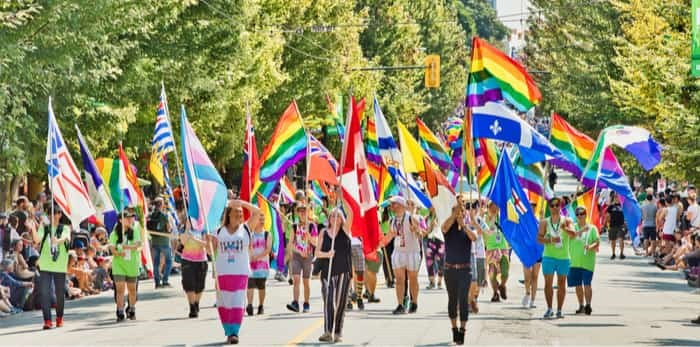 Vancouver, BC/Canada - August 5 2018 : Vancouver Pride Parade- People marching with rainbow flag / Shutterstock