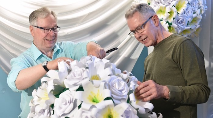 William Walker and Grant Kayler work on the flower arrangements at the Roundhouse community centre. Photo by Dan Toulgoet