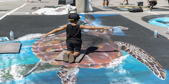 A young visitor interacts with chalk art by Wayne and Cheryl Renshaw at the 2018 Chalk Art Experience. Photo: Leanne Scherp, contributed (files)
