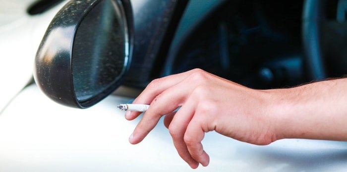 Smoking a cigarette in the car/Shutterstock