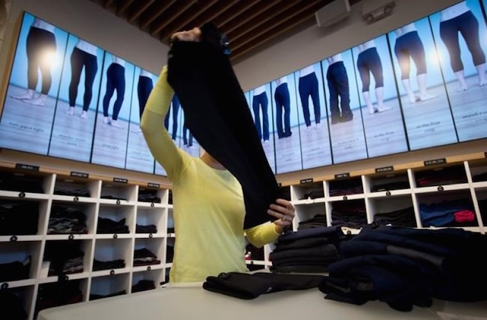 An employee folds yoga pants at a Lululemon Athletica store in Vancouver on August 21, 2014. The company wants customers to have more pea in their yoga pants. THE CANADIAN PRESS/Darryl Dyck