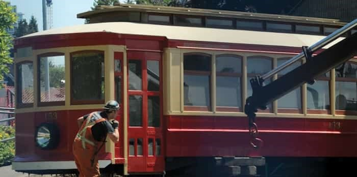 A crew from Nickel Bros. moving company inches the 111-year-old streetcar out from under the bleachers at Fen Burdett Stadium Wednesday. Photo: Mike Wakefield, North Shore News