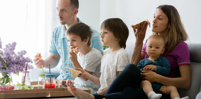 A young family eats dinner while watching television/Shutterstock