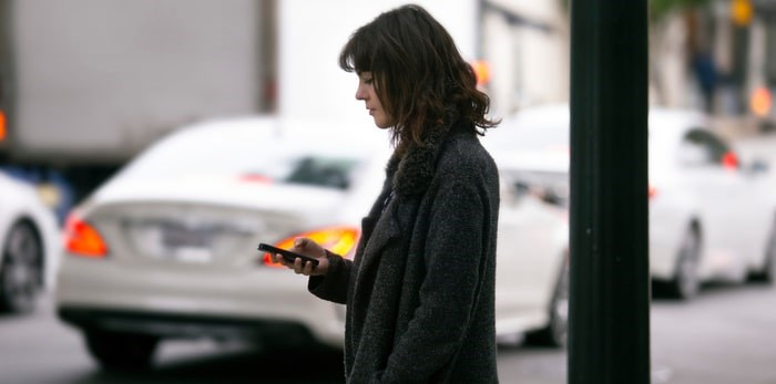 A ride-hailing customer waits for her car to pick her up/Shutterstock