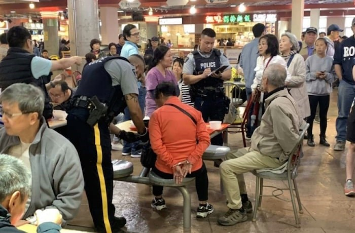 A photo posted on the Chinese social media channel WeChat shows an elderly couple being arrested at Crystal Mall after they allegedly threw soup into another woman's face Saturday. Screenshot/WeChat