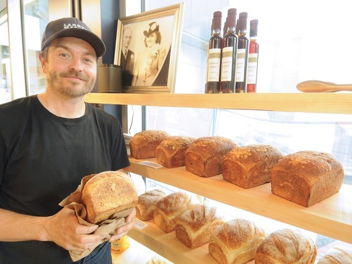 Larry's Market's Ryan Dennis stocks shelves with sourdough bread from The Modern Pantry. Photo by Mike Wakefield/North Shore News
