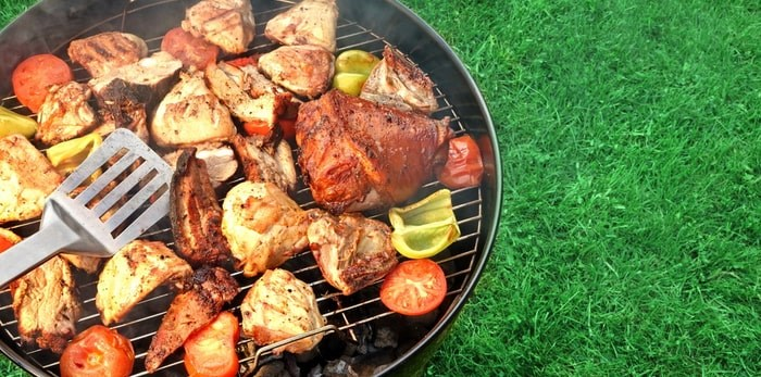Grilling meat and veggies on a backyard BBQ grill/Shutterstock