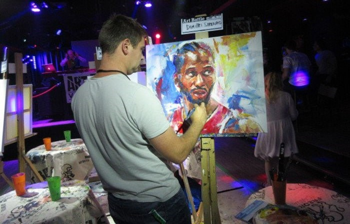 Vancouver Artist Dimitri Sirenko painting at an Art Battle event. Photo courtesy of Dimitri Sirenko